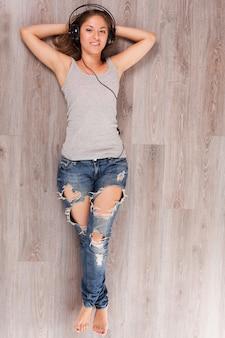 Piękna kobieta kłama na podłoga z hełmofonami