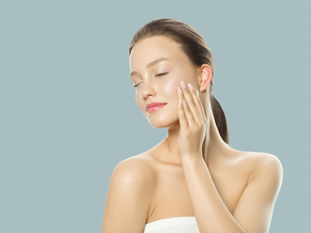 Piękna kobieta koncepcja pielęgnacji zdrowej skóry portret z bliska na niebieskim tle. strzał studio.