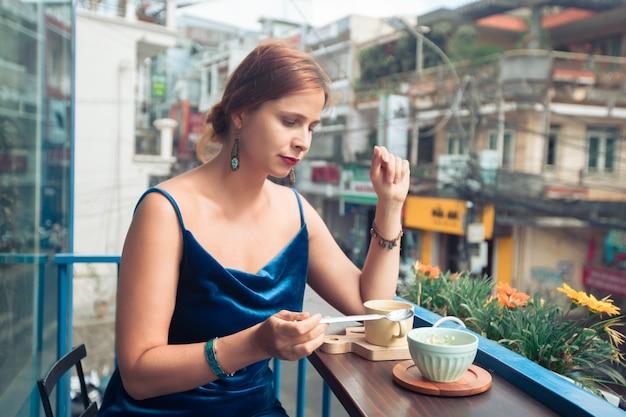 Piękna kobieta korzystająca z herbaty i deseru na tarasie kawiarni w dalat, wietnam.