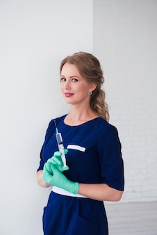 Piękna kobieta kosmetolog gospodarstwa strzykawki do leczenia przeciwstarzeniowego