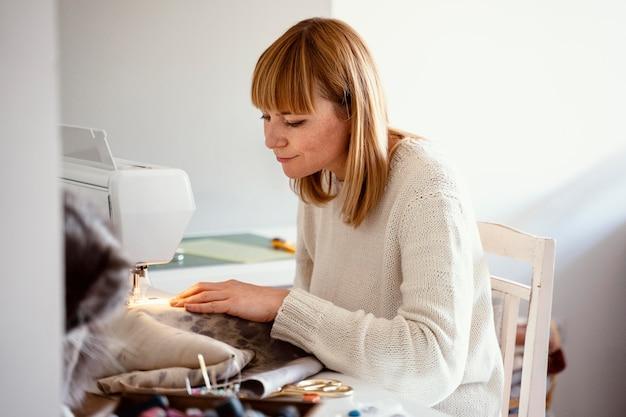 Piękna kobieta krawiec do szycia w swoim studio