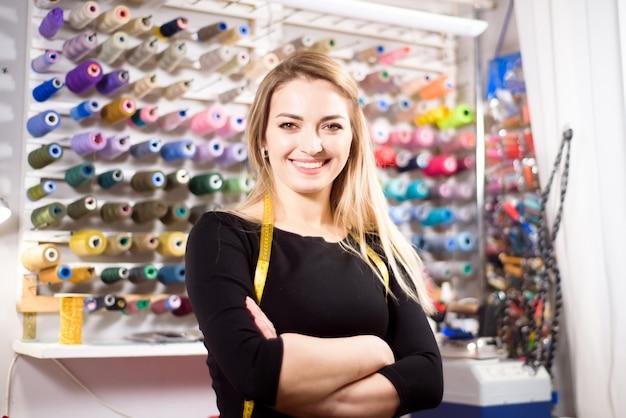 Piękna kobieta krawiecka na tle kolorowych szpulek nici do szycia i haftu.