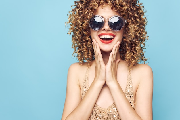 Piękna kobieta kręcone włosy uśmiech czerwone usta ręce na na białym tle twarzy niebieski