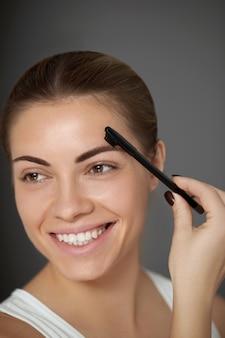Piękna kobieta kształtuje brwi grzebieniem. model piękna. makijaż brwi. korygowanie i konturowanie brwi.