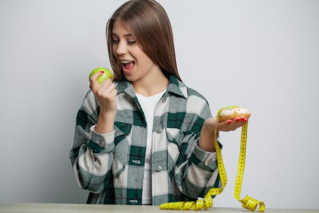 Piękna kobieta, która dokonuje wyboru między pożytecznym a szkodliwym pokarmem