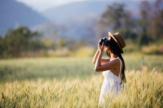 Piękna kobieta, która lubi strzelać na polach jęczmienia.