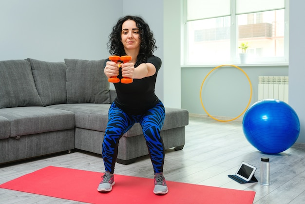 Piękna kobieta kuca z hantlami. pojęcie sportu, fitness i rekreacji.