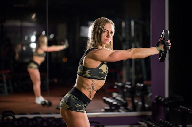 Piękna kobieta kulturysta z hantlami do podnoszenia. sportowa dziewczyna pokazująca dobrze wytrenowane ciało. dobrze rozwinięte mięśnie poprzez trening siłowy.
