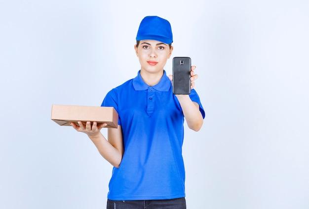 Piękna kobieta kurier pokazując opakowanie kartonowe i telefon komórkowy.