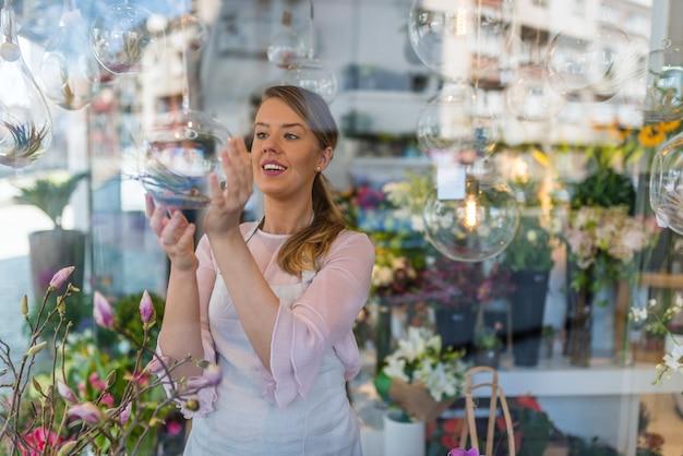 Piękna kobieta kwiaciarnia opiekuje się tillandsia.