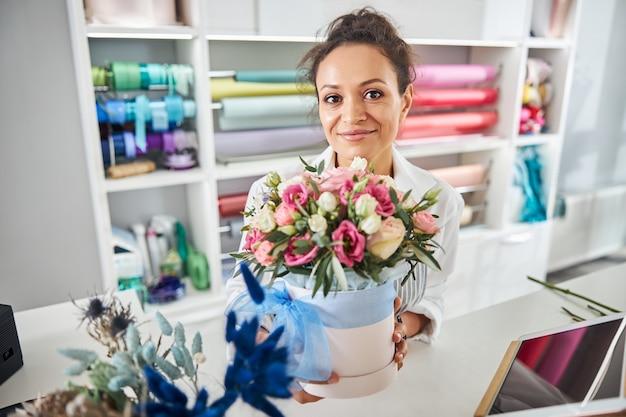 Piękna kobieta kwiaciarnia trzyma garnek z różami