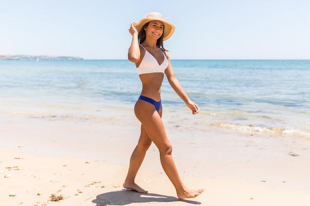 Piękna kobieta łacińskiej na plaży ucieka patrząc na kamery. portret szczęśliwa opalona kobieta uśmiecha się z morzem w tle.