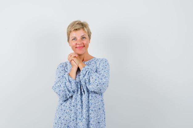 Piękna kobieta łączy ręce we wzorzystej bluzce i wygląda pozytywnie. przedni widok.