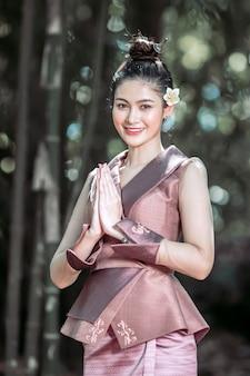 Piękna kobieta laosu w stroju ludowym podnosząca rękę, która jest symbolem pozdrowienia z laosu