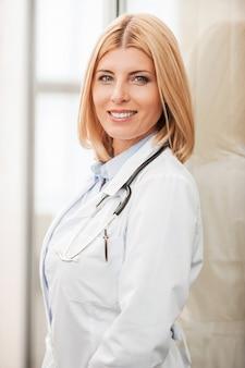 Piękna kobieta lekarz. widok z boku pewnej siebie lekarki w białym mundurze, patrzącej na kamerę i uśmiechającej się, opierając się o szklaną ścianę
