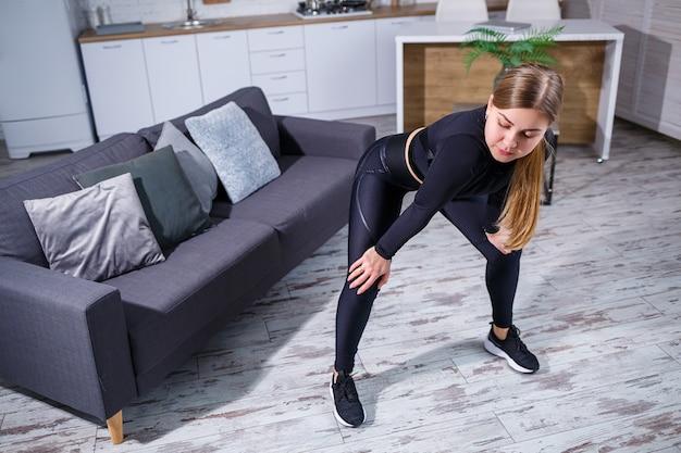 Piękna kobieta lekkoatletycznego w czarny top i legginsy uprawiania sportu w domu. motywacja do uprawiania sportu. zdrowy tryb życia.