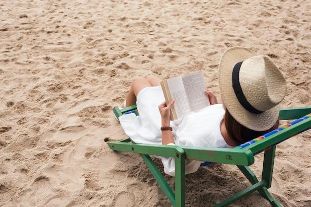 Piękna kobieta leżąca i czytająca książkę na leżaku z uczuciem relaksu