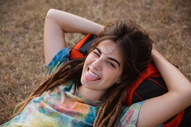 Piękna kobieta leżała na trawie patrząc aparat cieszyć się podróżowaniem