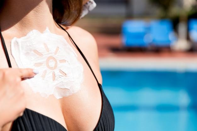 Piękna kobieta ma krem przeciwsłoneczny w kształcie słońca na piersi przy basenie. współczynnik ochrony przeciwsłonecznej na wakacjach, koncepcja.
