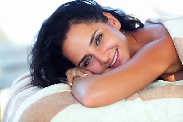 Piękna kobieta ma masaż na słonecznej plaży