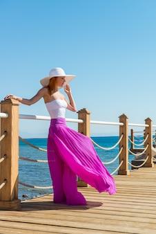 Piękna kobieta ma na sobie kapelusz i spódnica różowy