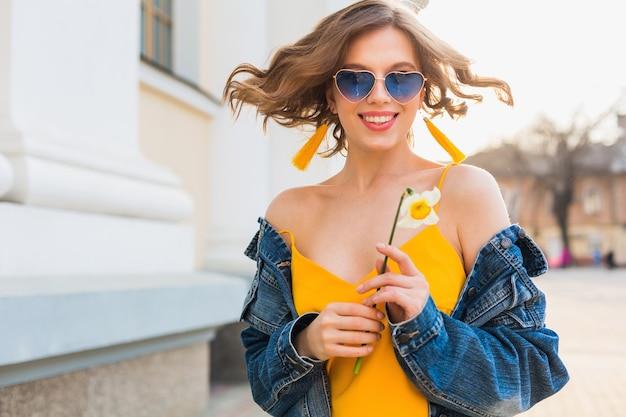 Piękna kobieta macha włosami uśmiechnięta, stylowa odzież, ubrana w dżinsową kurtkę i żółty top, trend w modzie, styl letni, szczęśliwy pozytywny nastrój, słoneczny dzień, wschód słońca, moda uliczna, niebieskie okulary przeciwsłoneczne