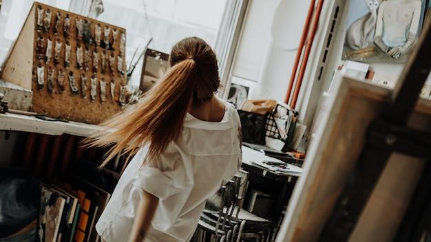 Piękna kobieta malarz na sobie białą koszulę taniec podczas malowania w warsztacie artystycznym. selektywne skupienie. zdjęcie w stylu vintage
