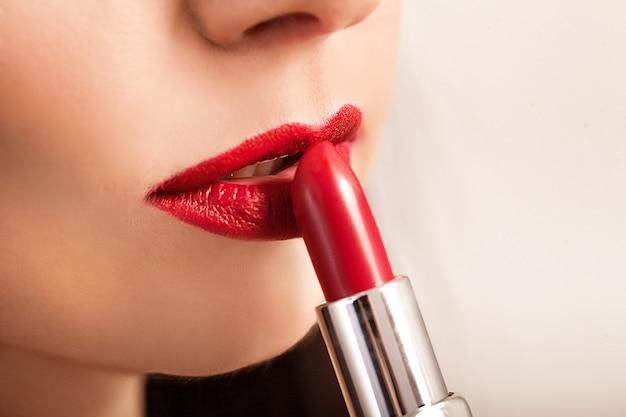 Piękna kobieta maluje usta szminką.