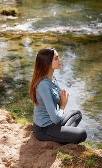 Piękna kobieta, medytując w przyrodzie