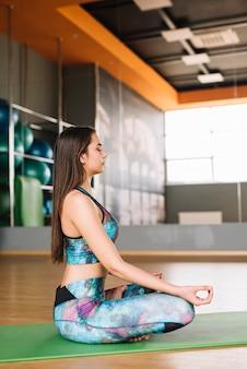 Piękna kobieta medytuje siedzieć na joga macie