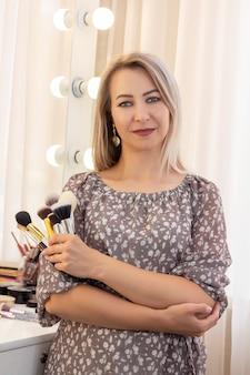 Piękna kobieta mistrz makijażu. stojący z pędzlami do makijażu w rękach. zdjęcie pionowe