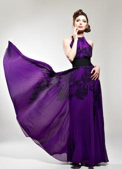 Piękna kobieta moda w fioletowy długa sukienka fryzura z warkoczykami, pozuje w studio