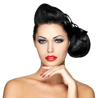 Piękna kobieta moda z czerwonymi ustami, paznokciami i kreatywną fryzurą - na białym tle na białej ścianie