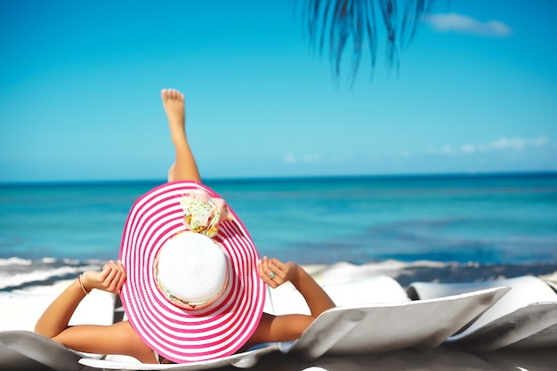 Piękna kobieta model opalając się na krześle plaży w białym bikini w kolorowe sunhat za niebieski lato woda ocean