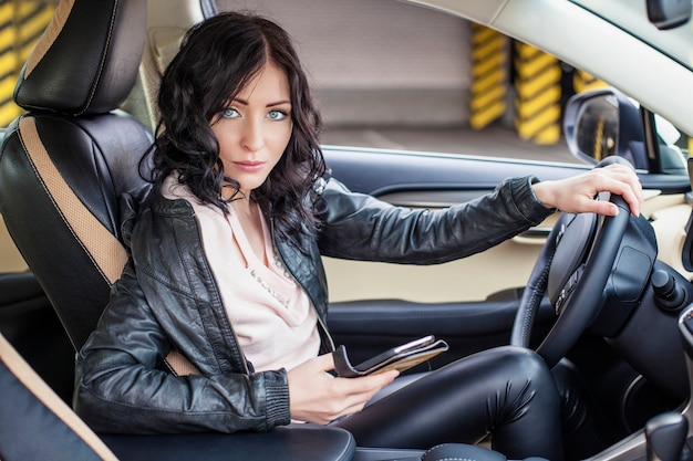 Piękna kobieta model siedzi w samochodzie z telefonem w ręku i wpisując wiadomość