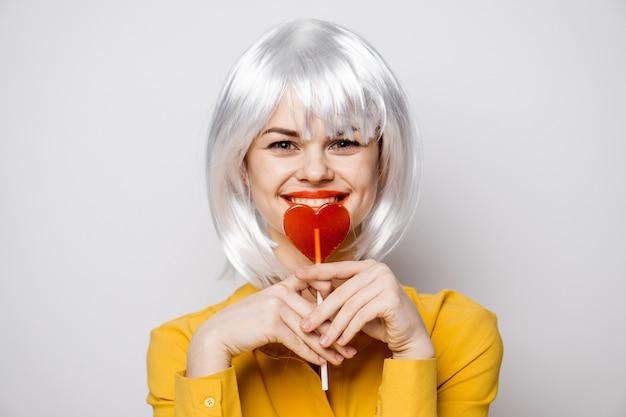 Piękna kobieta model z lizakiem serca przy stole w żółtej koszuli wywołuje różne emocje. walentynki
