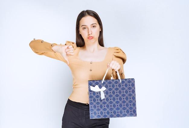 Piękna kobieta model z torbą na zakupy pokazując kciuk w dół.