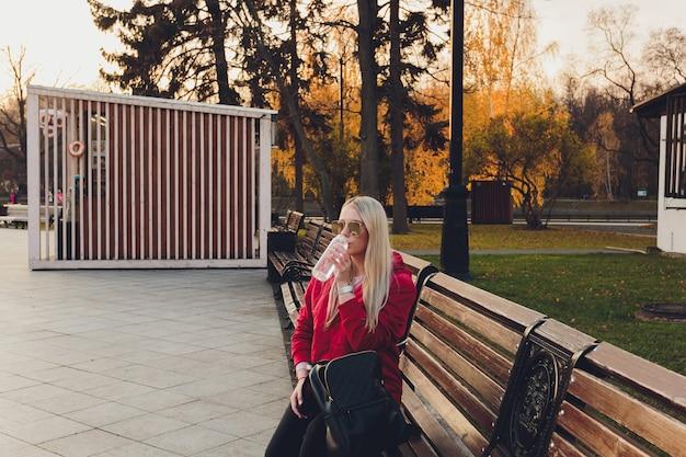 Piękna kobieta mody z torebką siedzi i czeka na ławce w parku