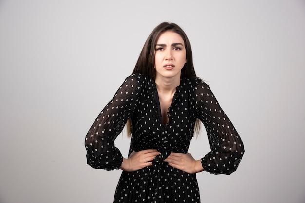 Piękna kobieta mówi trzymając się za brzuch z powodu bólu.