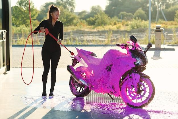 Piękna kobieta, mycie motocykla