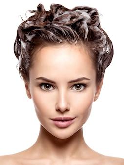 Piękna kobieta myje brązowe włosy na białej ścianie
