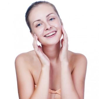 Piękna kobieta myje jej twarz na bielu