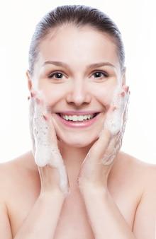 Piękna kobieta myje jej twarz - odizolowywającą na bielu