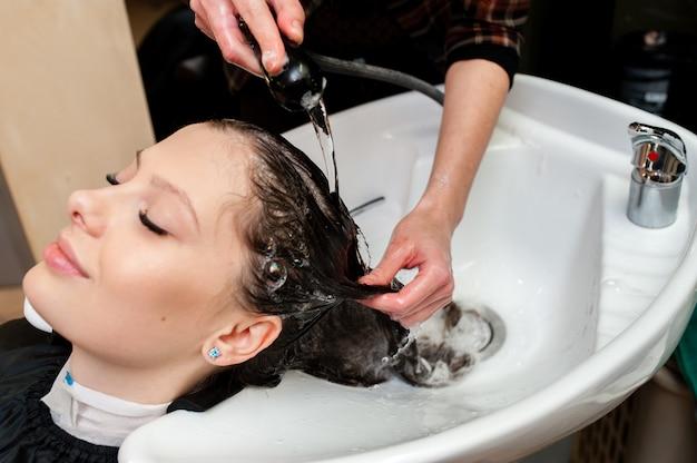 Piękna kobieta myje włosy w salonie