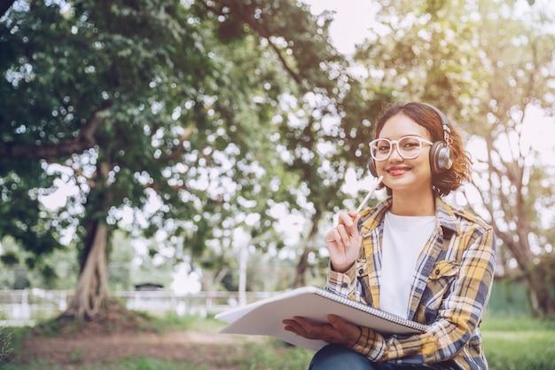 Piękna kobieta myśli i pisze notatki na papierze w parku