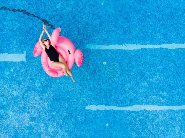 Piękna kobieta na basenie flamingów unosi się w basenie, widok z lotu ptaka drona