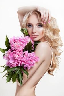 Piękna kobieta na białej ścianie z bukietem różowych kwiatów piwonii