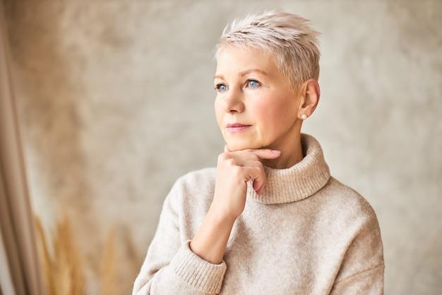 Piękna kobieta na emeryturze, ubrana w wygodny sweter i krótką fryzurę