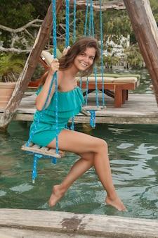 Piękna kobieta na huśtawkach które nad woda