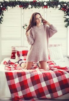 Piękna kobieta na łóżku w kratę w boże narodzenie